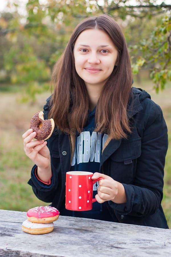 Het glimlachende meisje eet donuts met koffie op een houten lijst stock foto's