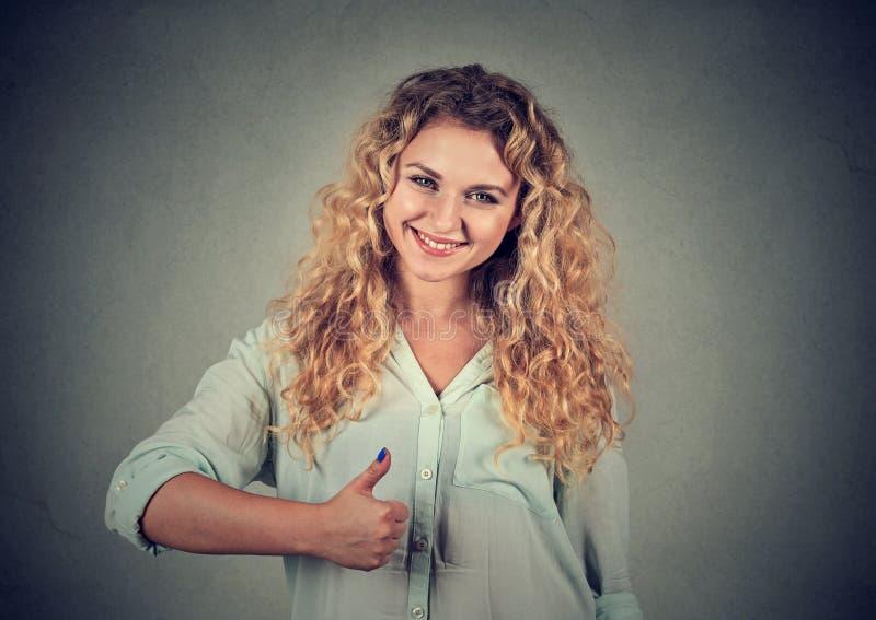 Het glimlachende meisje heft omhoog juiste duim op stock foto