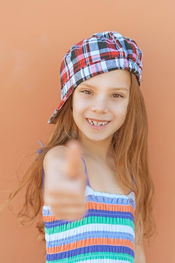 Het glimlachende meisje in kleding heft duim-omhoog op stock afbeelding