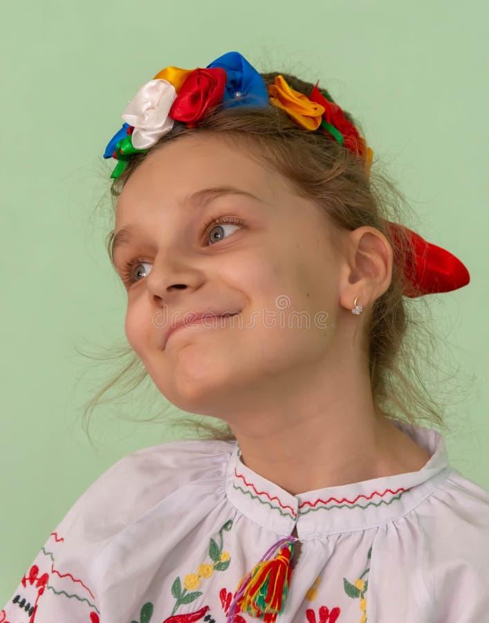 Het glimlachende meisje kleedde zich in nationaal geïsoleerd kostuum stock fotografie