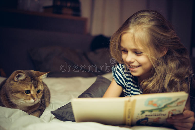 Het glimlachende meisje leest boek aan een kat royalty-vrije stock afbeeldingen