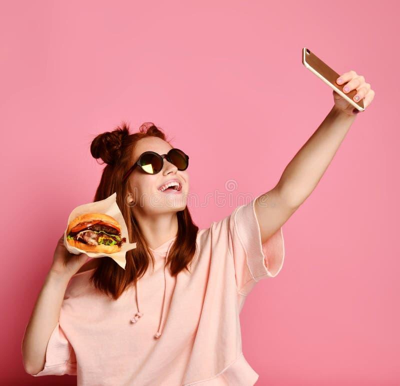 Het glimlachende meisje in levensstijl kleedt het nemen van beeld zelfportret op smartphone met hamburgersandwich stock foto