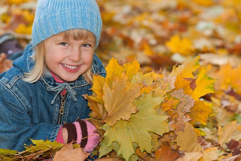 Het glimlachende meisje ligt op de gele bladeren royalty-vrije stock foto's