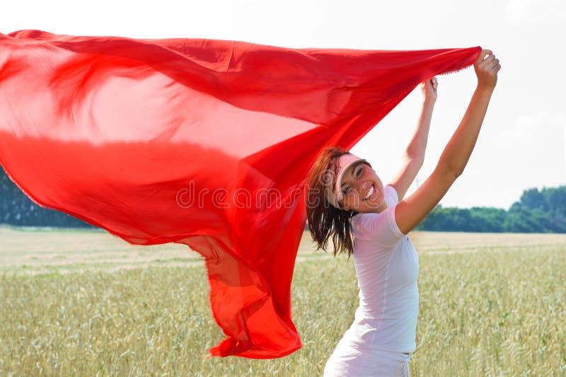 Het glimlachende meisje met een rode sjaal stock foto's