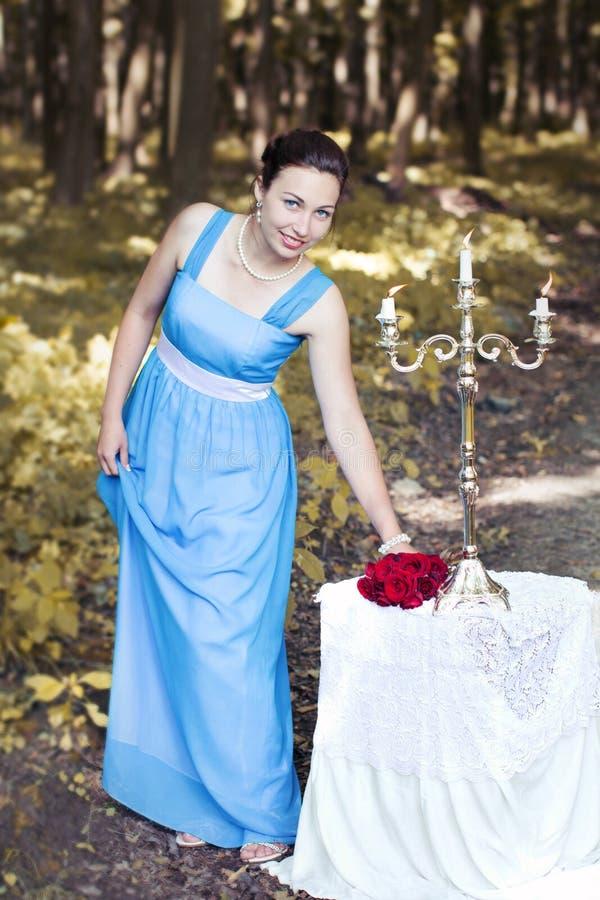 Het glimlachende meisje neemt een boeket van rode rozen van een lijst royalty-vrije stock foto's