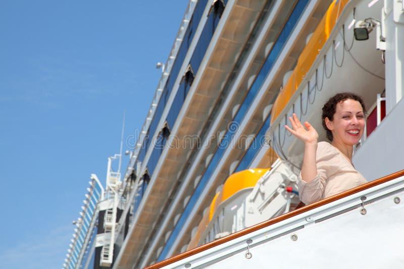 Het glimlachende meisje op ladder gaat naar het grote cruiseschip stock afbeelding