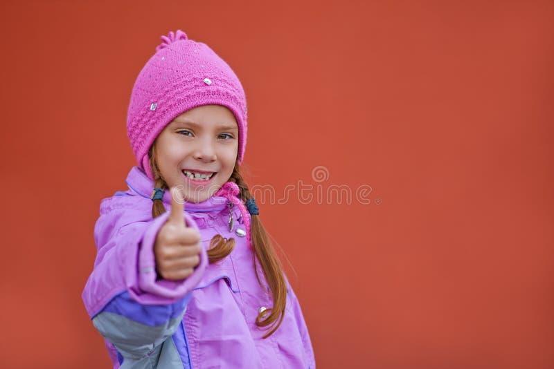 Het glimlachende meisje in roze kleding heft op royalty-vrije stock foto's