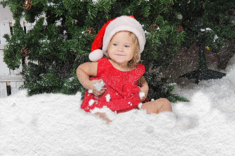 Het glimlachende meisje in santakostuum zit op sneeuw royalty-vrije stock afbeeldingen