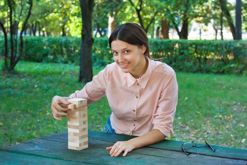 Het glimlachende meisje speelt een houten blokspel stock foto's