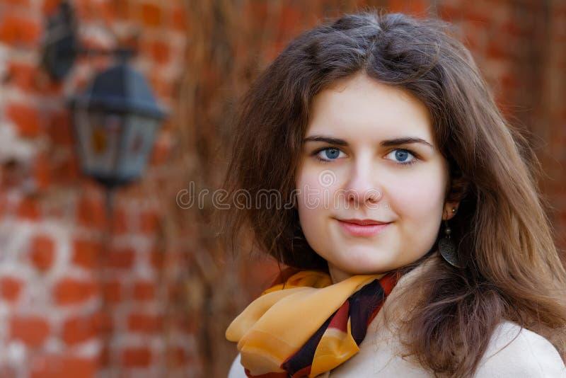 Het glimlachende meisje tegen een muur stock foto's