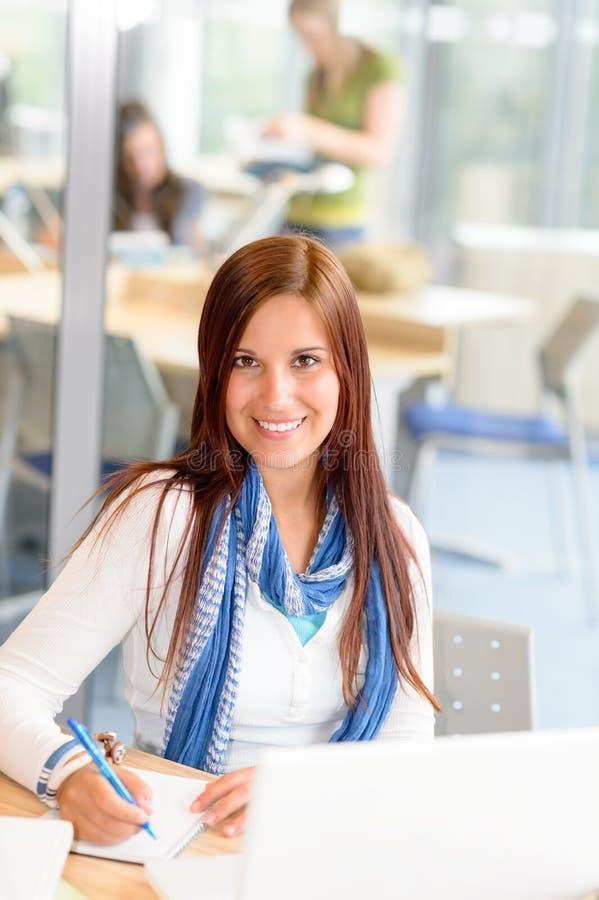 Het glimlachende meisje van de middelbare schoolstudent neemt nota's royalty-vrije stock afbeelding