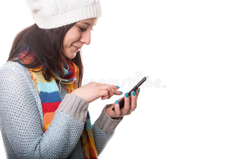 Het glimlachende Meisje van de Winterhipster in Gebreide Sweater en Beanie Hat met Mobiele die Telefoon op Wit wordt geïsoleerd T stock foto