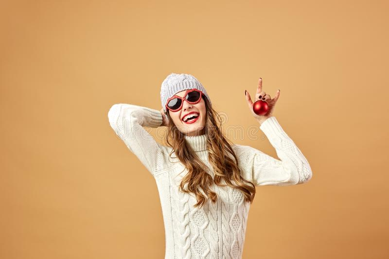 Het glimlachende meisje in zonnebril gekleed in witte gebreide sweater en hoed houdt een rode Kerstmisbal op een beige achtergron stock afbeeldingen