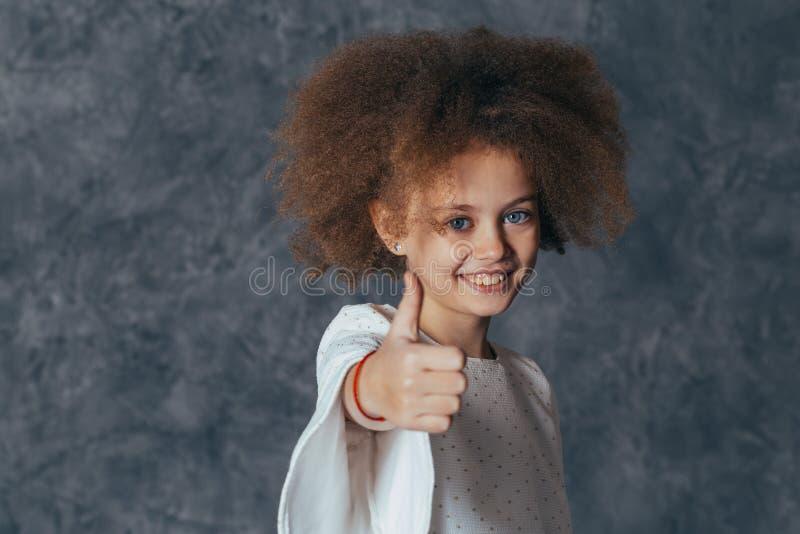 Het glimlachende mooie meisje met krullend haar toont duim royalty-vrije stock afbeelding