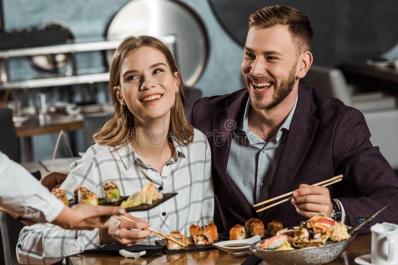 Het glimlachende paar die sushi eten rolt terwijl kelner die nieuwe orde brengen royalty-vrije stock afbeelding
