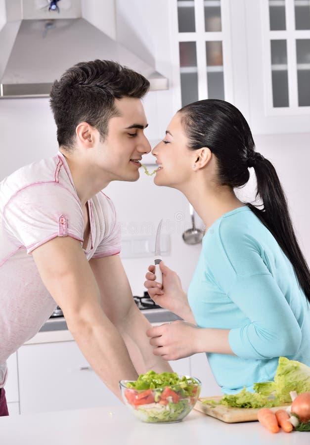 Het glimlachende paar eet salade in de keuken stock fotografie