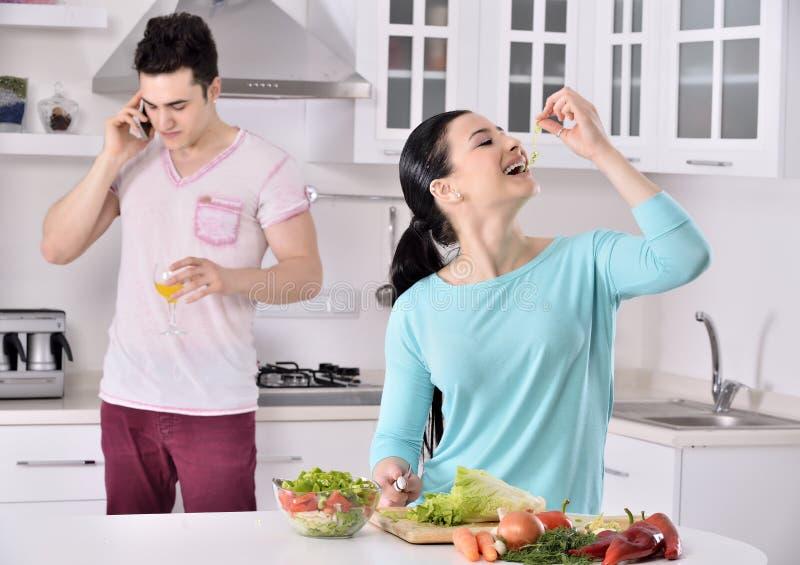 Het glimlachende paar eet salade in de keuken stock afbeelding