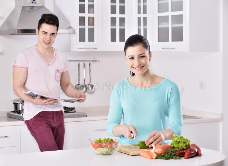 Het glimlachende paar eet salade in de keuken royalty-vrije stock afbeeldingen