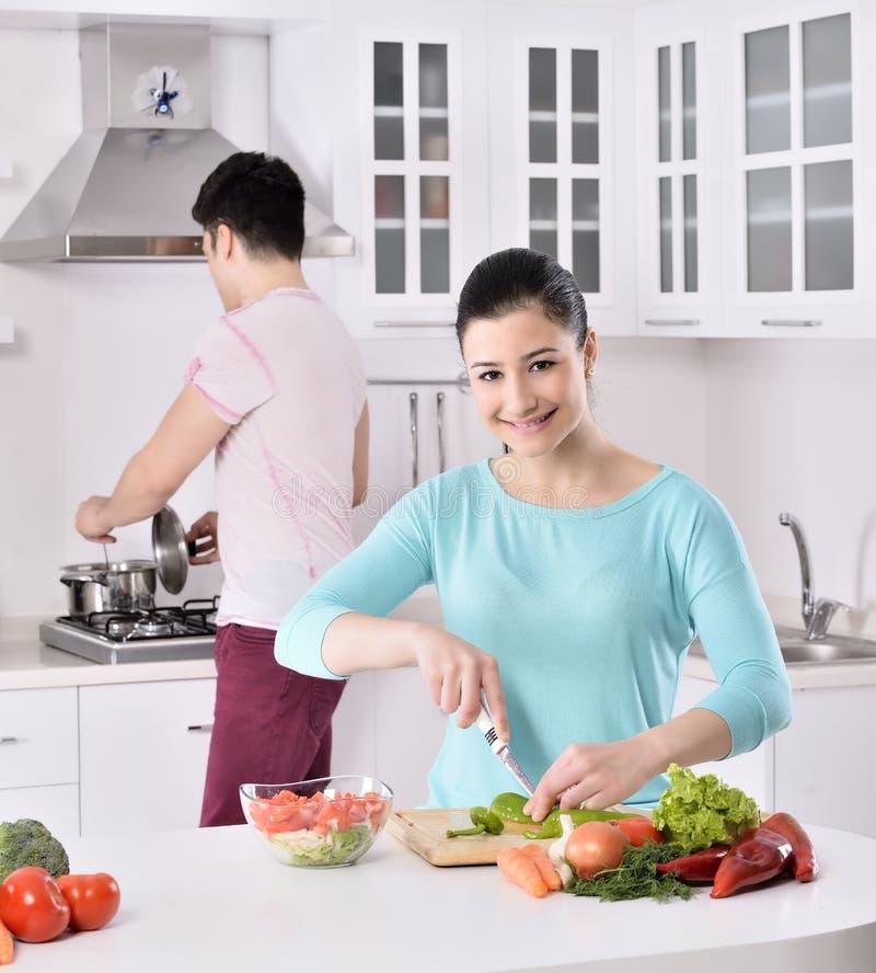 Het glimlachende paar eet salade in de keuken royalty-vrije stock afbeelding