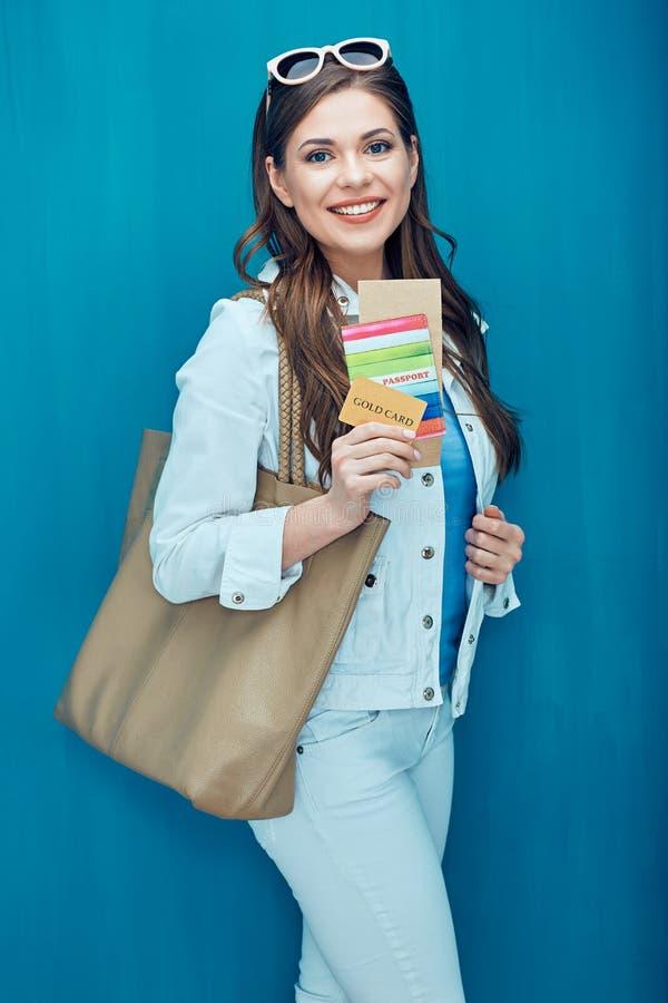 Het glimlachende paspoort van de vrouwenholding en creditcard klaar voor vakantiereis