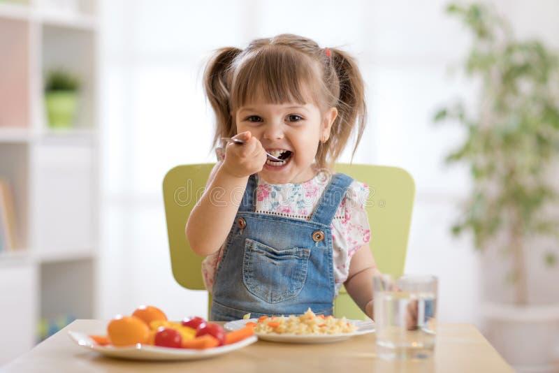 Het glimlachende peutermeisje eet thuis stock afbeelding