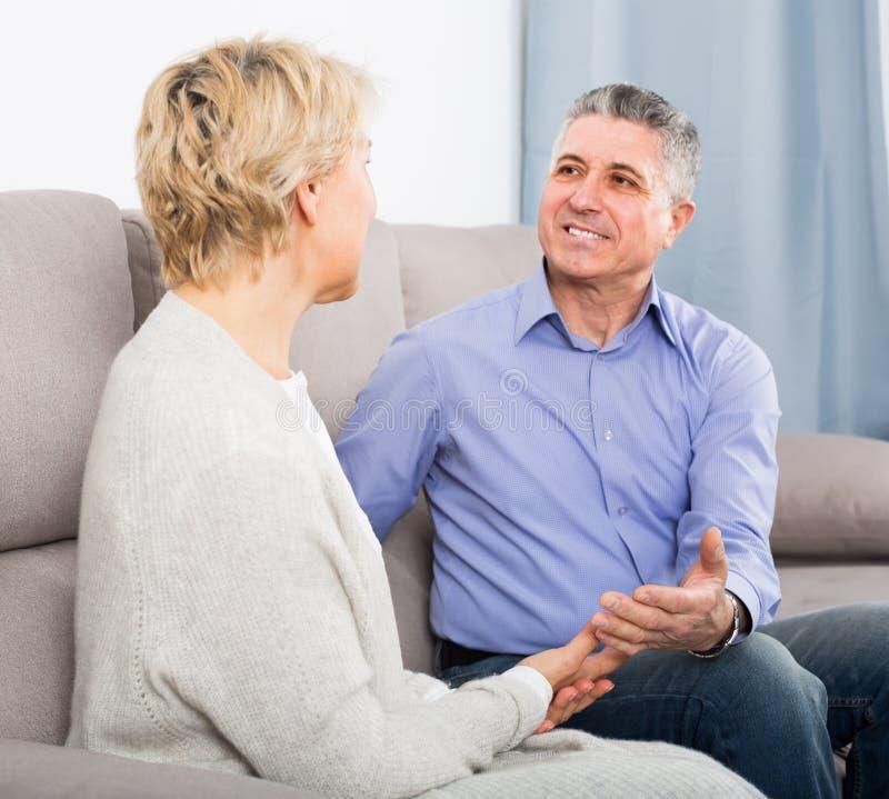 Het glimlachende rijpe echtpaar wordt binnenshuis warm achterin verzoend stock foto