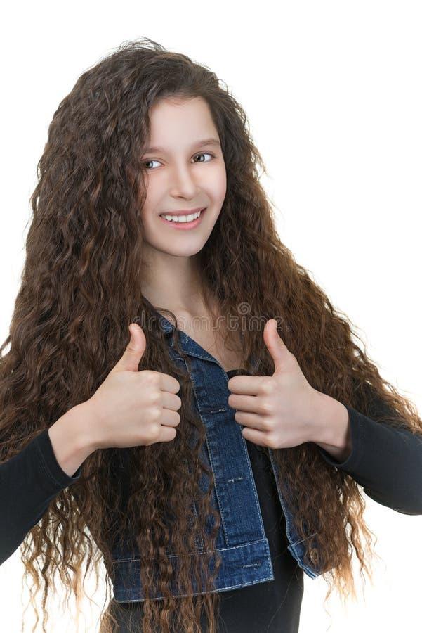 Het glimlachende schoolmeisje heft duim-omhoog op stock fotografie
