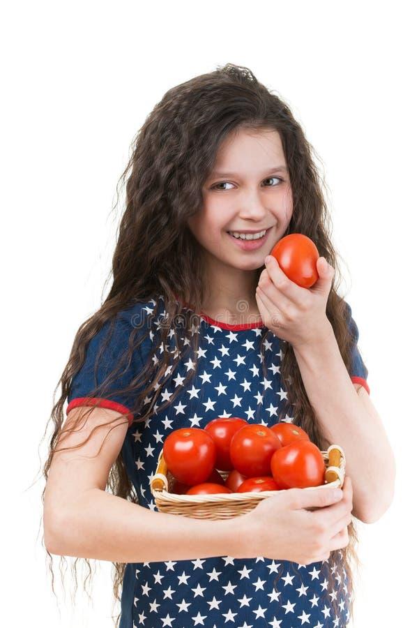 Het glimlachende schoolmeisje houdt mand van tomaat stock foto