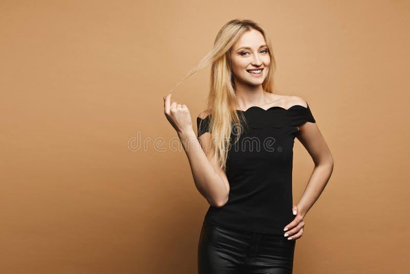 Het glimlachende, sexy en mooie blonde modelmeisje met perfect lichaam in zwart leer hijgt en zwarte t-shirt aanpassend haar haar royalty-vrije stock afbeelding