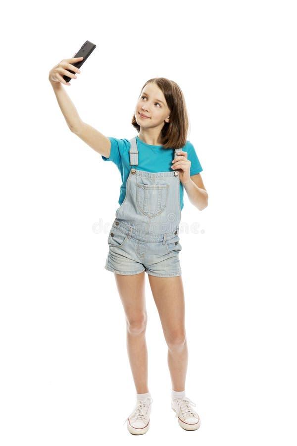 Het glimlachende tienermeisje wordt gefotografeerd op de telefoon volledige hoogte Close-up Ge?soleerd op een witte achtergrond stock foto