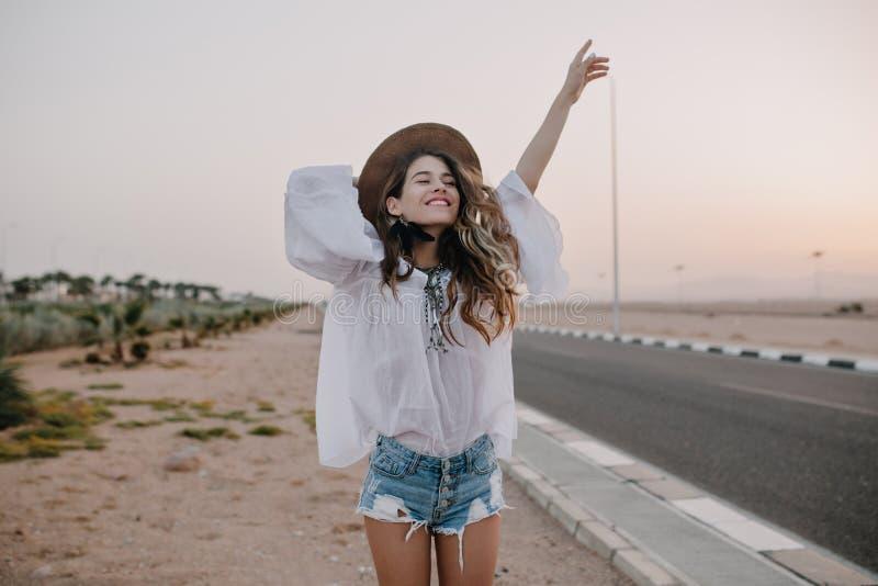 Het glimlachende vrolijke langharige meisje met krullend haar ademt volledige borst en geniet van vrijheid, die zich naast weg be royalty-vrije stock afbeeldingen