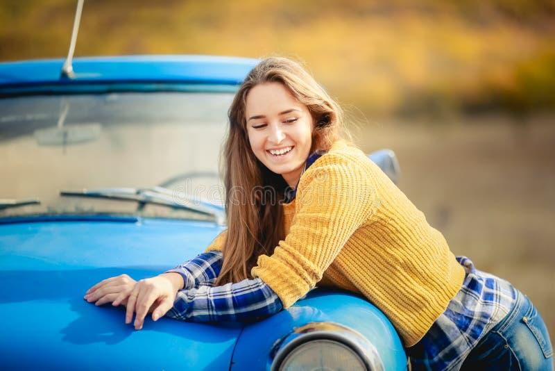 Het glimlachende vrolijke meisje met lang haar, die in zwarte hoed en gele sweater dragen, en geniet van vrijheid, die zich naast royalty-vrije stock foto's
