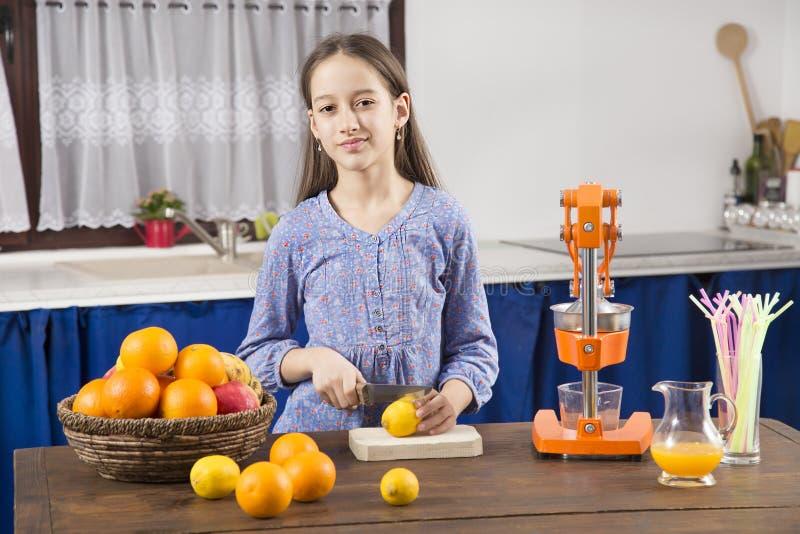 Het glimlachmeisje in keuken maakt een sap royalty-vrije stock fotografie