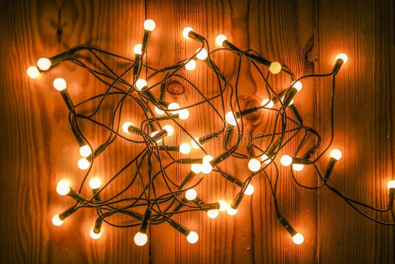 Het gloeien Kerstboomlichten die op een houten vloer liggen stock fotografie