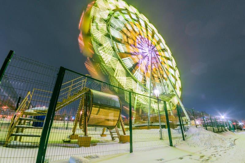 Het gloeiende wiel van aantrekkelijkheidsferris bij nacht in de winter stock afbeelding