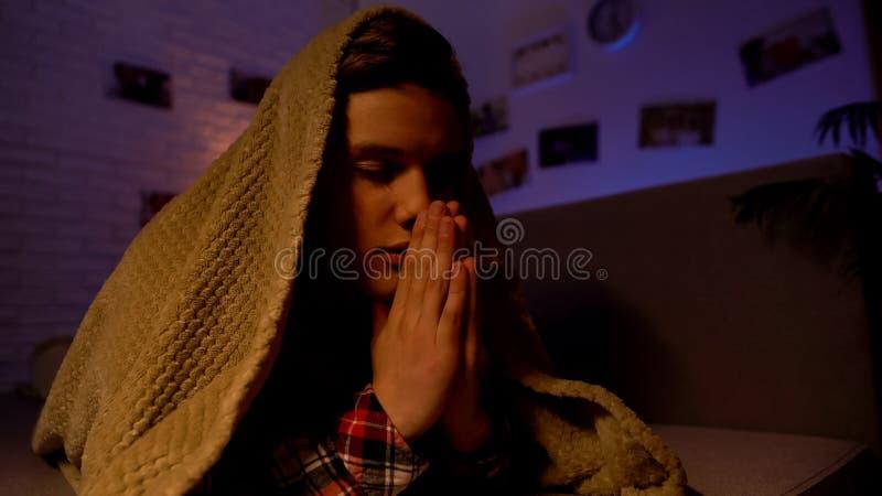Het godsdienstige tiener bidden behandeld met deken, overtuiging in god, sektarisme royalty-vrije stock foto
