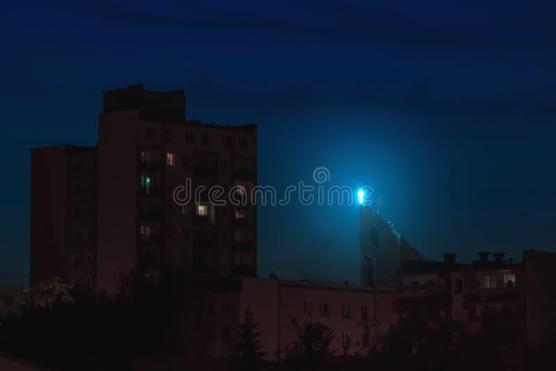 Het godsdienstkruis verlichtte hoog dak boven stadsgebouwen bij nacht stock foto's