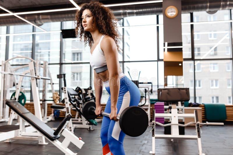 Het goede geschikte krullende meisje gekleed in sportenkleren doet deadlift met barbell in het moderne gymnastiekhoogtepunt van z royalty-vrije stock foto's
