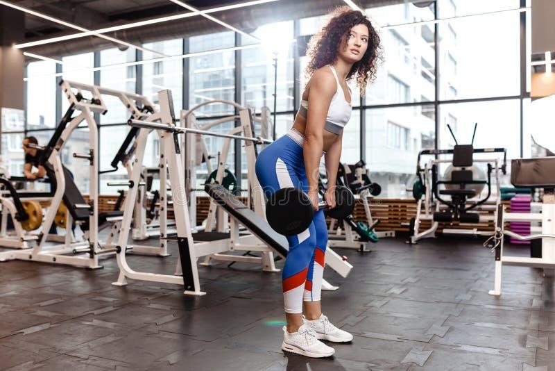 Het goede geschikte krullende meisje gekleed in sportenkleren doet deadlift met barbell in het moderne gymnastiekhoogtepunt van z royalty-vrije stock afbeelding