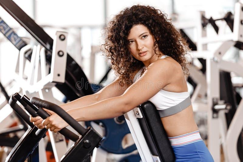 Het goede geschikte krullende meisje gekleed in sportenkleren doet oefening op de sportuitrusting in het moderne gymnastiekhoogte stock foto