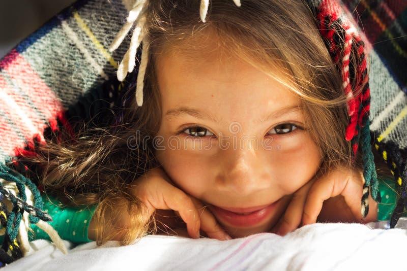 Het goedemorgenportret van leuk krullend glimlachend schoolmeisje kijkt uit van warme plaid stock fotografie