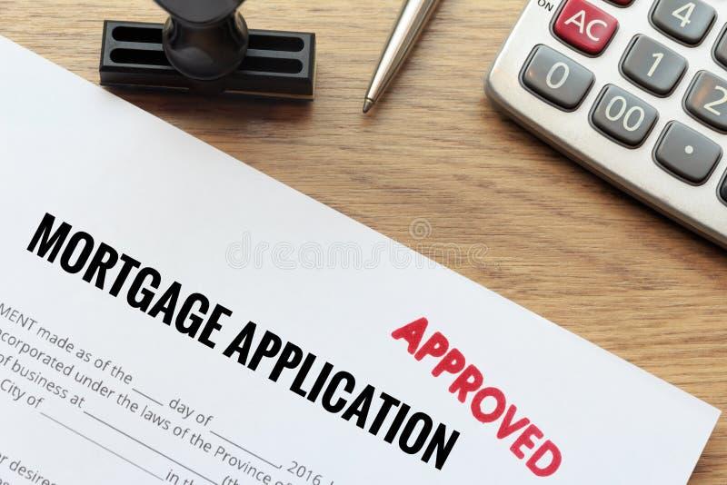 Het goedgekeurde hypotheekaanvraagformulier bepaalt op houten bureau met royalty-vrije stock foto's
