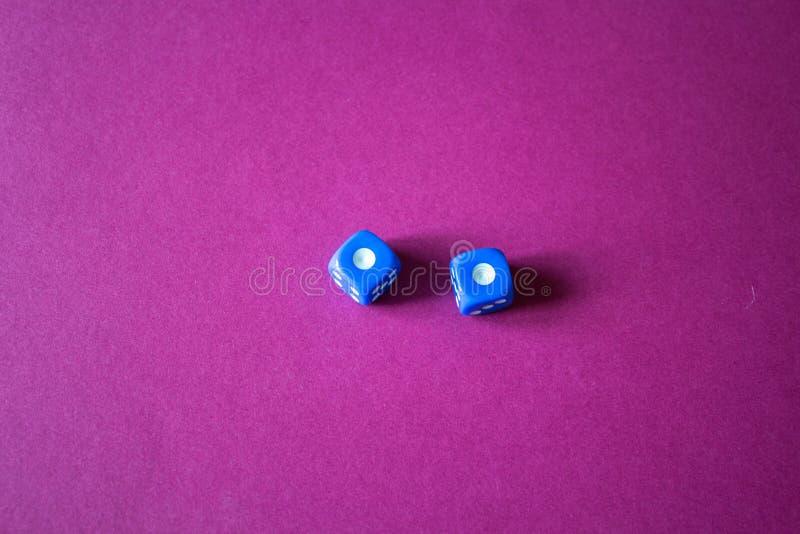 Het gokken dobbelt op een rode achtergrond stock afbeeldingen