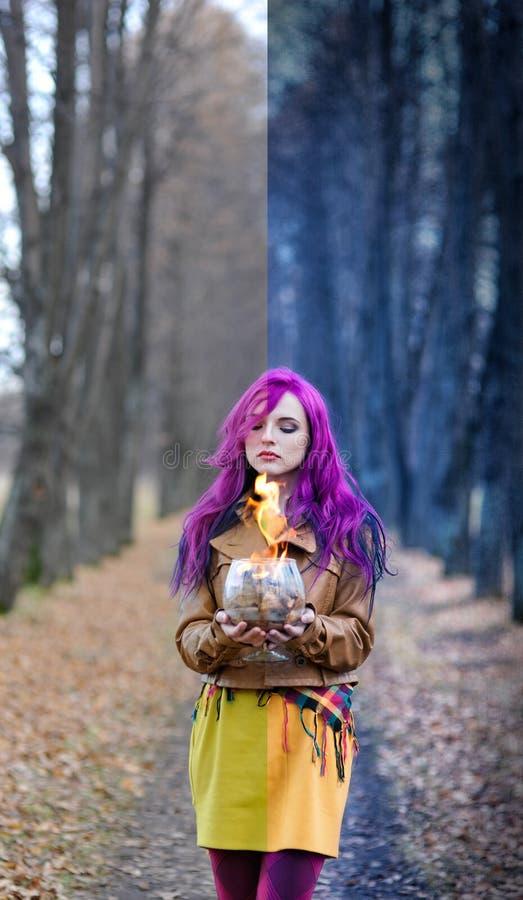 Het gotische Meisje met purper haar bevindt zich met een brandglas in haar indient de steeg in de herfst het bosconcept uitgeven, stock afbeeldingen