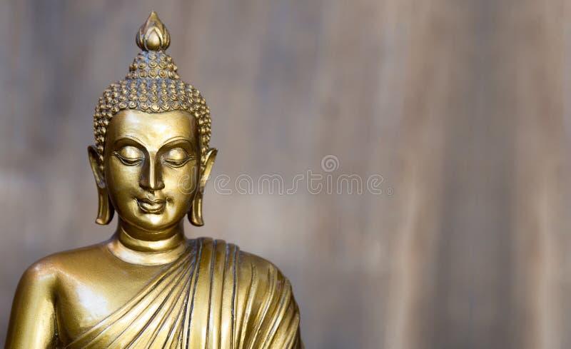 Het gouden antieke standbeeld van Boedha De achtergrond is lichte grijze lei Het gezicht van Boedha draaide aan recht stock fotografie