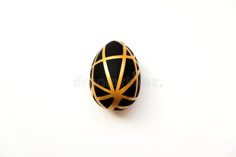 Het gouden ei van Pasen met geometrisch zwart die patroon op witte achtergrond wordt geïsoleerd Minimaal Pasen-concept Hoogste fl royalty-vrije stock afbeeldingen