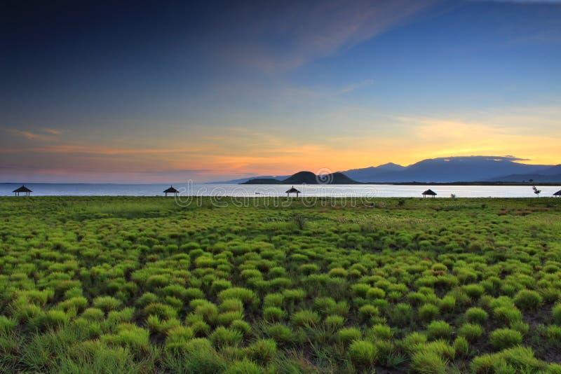 Het gouden licht zet hierboven Rinjani op zoals die van Kenawa-Eiland, Sumbawa, Indonesië wordt gezien stock foto