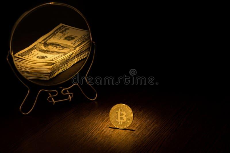 Het Gouden Muntstuk van Bitcoin wordt weerspiegeld in een spiegel in de vorm van een pak van honderd dollarsrekeningen, een bedri stock fotografie