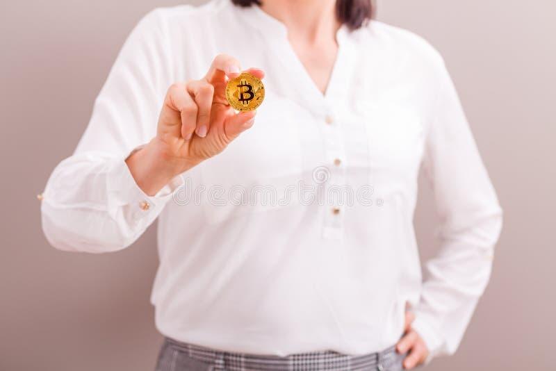Het gouden muntstuk van de onderneemsterholding bitcoin stock foto