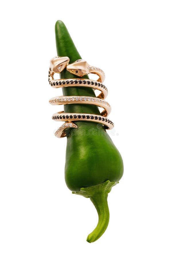 Het gouden ringvormige kussen kronkelt met zirkonen en zwarte diamanten versleten op geïsoleerde peper, stock afbeelding